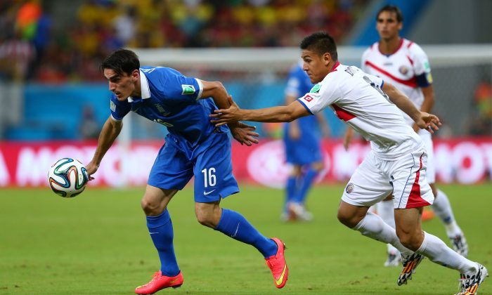Oscar Duarte of Costa Rica challenges Lazaros Christodoulopoulos of Greece during the 2014 FIFA World Cup Brazil Round of 16 match between Costa Rica and Greece at Arena Pernambuco on June 29, 2014 in Recife, Brazil. (Quinn Rooney/Getty Images)