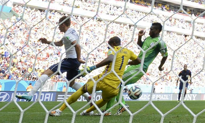 Nigeria's defender Joseph Yobo (R) scores an own goal while challenging France's forward Antoine Griezmann (L) during the round of 16 football match between France and Nigeria at the Mane Garrincha National Stadium in Brasilia during the 2014 FIFA World Cup on June 30, 2014. (FRANCK FIFE/AFP/Getty Images)