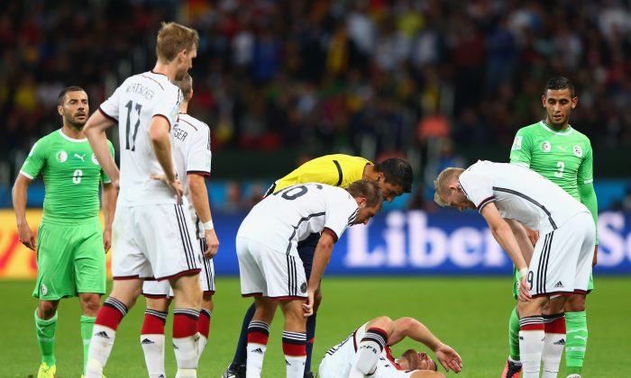 Shkodran Mustafi of Germany lies on the field as his teammates and referee Sandro Ricci look on during the 2014 FIFA World Cup Brazil Round of 16 match between Germany and Algeria at Estadio Beira-Rio on June 30, 2014 in Porto Alegre, Brazil. (Jamie Squire/Getty Images)