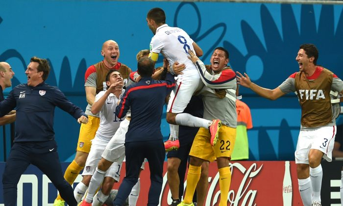 United States' Clint Dempsey celebrates with his teammates after scoring his side's second goal during the group G World Cup soccer match between the USA and Portugal at the Arena da Amazonia in Manaus, Brazil, Sunday, June 22, 2014. (AP Photo/Paulo Duarte)