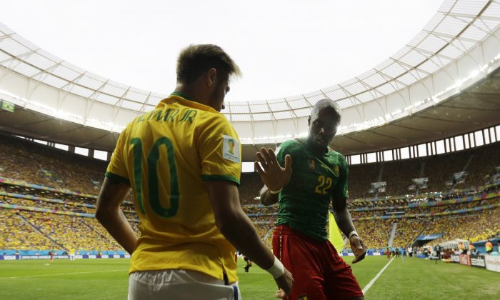 Cameroon's Allan Nyom tries to shake hands with Brazil's Neymar after pushing him to the ground in the corner during the group A World Cup soccer match between Cameroon and Brazil at the Estadio Nacional in Brasilia, Brazil, Monday, June 23, 2014. (AP Photo/Natacha Pisarenko)
