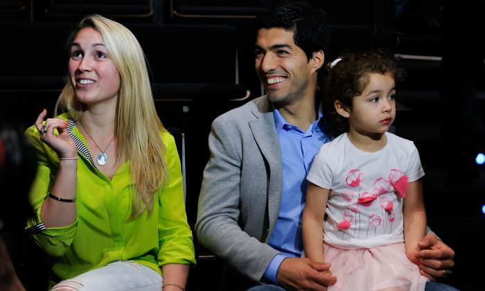 Luis Suarez of Liverpool and his wife Sofia Balbi sit with their daughter Delfina during the presentation as new Ambassador for 888poker on May 14, 2014 in Barcelona, Spain. (David Ramos/Getty Images)