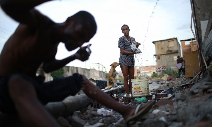 A woman washes clothes from a small hose amongst the remains of homes demolished to make way for World Cup construction that never happened near the Maracana stadium in Rio de Janeiro, Brazil, on May 22, 2014. The World Cup  has fallen short of its lofty environmental goals, but its legacy could be a shift in how global sporting events address social injustice. (Mario Tama/Getty Images)
