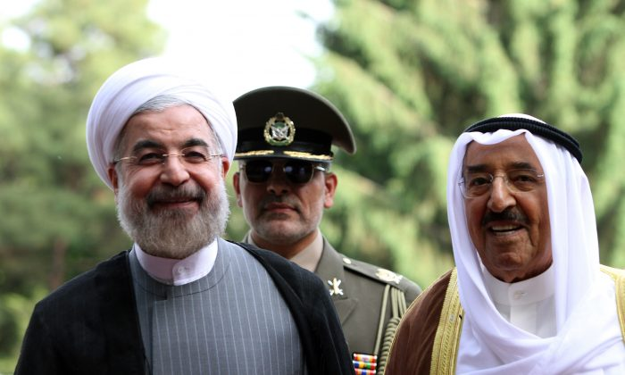 Iranian President Hassan Rouhani (L) and Emir of Kuwait, Sheikh Sabah al-Ahmad al-Sabah (R) review the honor guard during a welcoming ceremony for the Emir upon his arrival in Tehran on June 1, 2014. Kuwait's Emir started a landmark visit to Tehran focused on mending fences between Shiite Iran and the Sunni-ruled monarchies in the Gulf. (Atta Kenare/AFP/Getty Images)