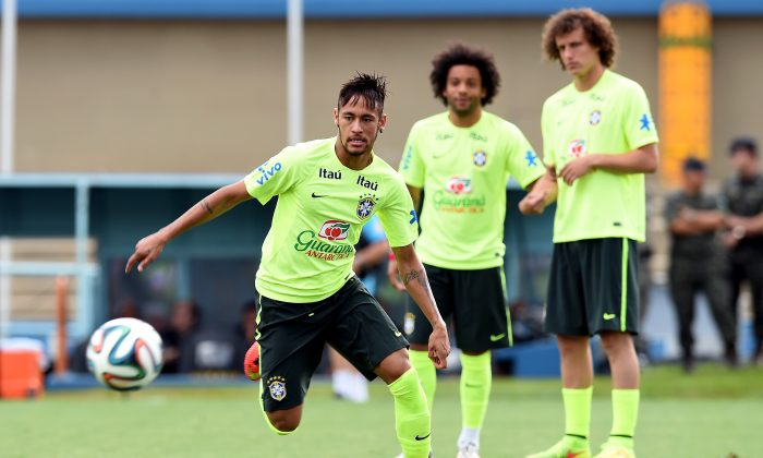 Brazilian forward Neymar (L) takes the ball observed by defenders Marcelo (C) and David Luiz during a national team training session in Serra Dourada Stadium in Goiania, Goias, on June 02, 2014. Brazil faces Panama on June 3 as preparation for the FIFA World Cup Brazil 2014 that starts on June 12. (AFP/Getty Images)