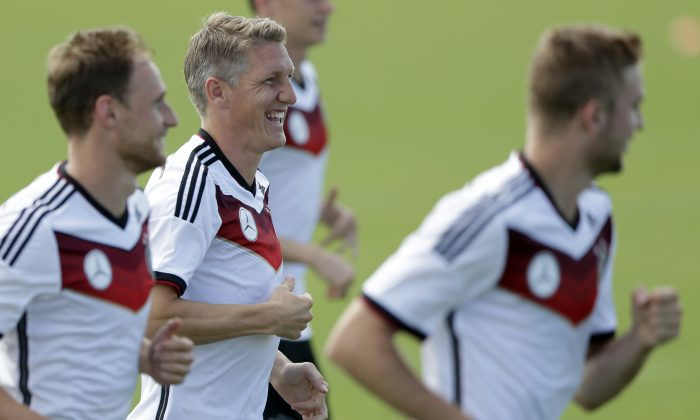 German national soccer player Bastian Schweinsteiger, center, laughs during a training session in Santo Andre near Porto Seguro, Brazil, Saturday, June 14, 2014. Germany will play in group G of the 2014 soccer World Cup. (AP Photo/Matthias Schrader)