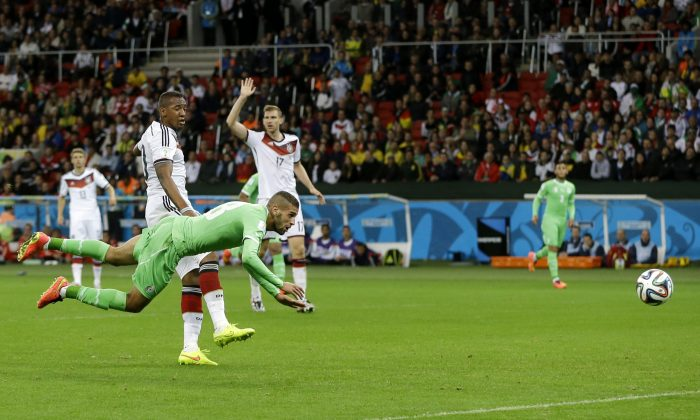Algeria's Islam Slimani is airborne in front of Germany's Jerome Boateng after heading the ball at Germany's goal during the World Cup round of 16 soccer match between Germany and Algeria at the Estadio Beira-Rio in Porto Alegre, Brazil, Monday, June 30, 2014.  (AP Photo/Kirsty Wigglesworth)