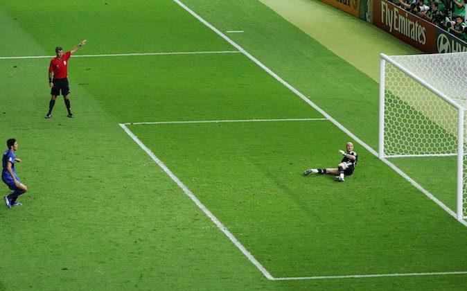 Fabio Grosso (L) of Italy takes the matchwinning penalty, as Goalkeeper Fabien Barthez (2nd R) of France dives the wrong way during the FIFA World Cup Germany 2006 Final match between Italy and France at the Olympic Stadium on July 9, 2006 in Berlin, Germany. (Mike Hewitt/Getty Images)