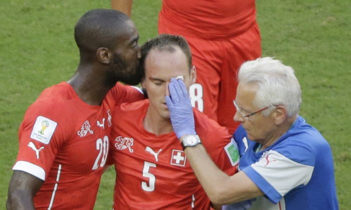 Switzerland's Johan Djourou, left, kisses his injured teammate Steve von Bergen during the group E World Cup soccer match between Switzerland and France at the Arena Fonte Nova in Salvador, Brazil, Friday, June 20, 2014. (AP Photo/Sergei Grits)