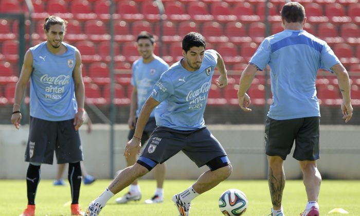 Martin Carceres and Jorge Fucili, back, observes Luis Suarez, center, dribble at a practice session at Arena do Jacare Stadium, for the Brazil 2014 World Cup in Sete Lagoas, Brazil, Saturday, June 21, 2014. Uruguay plays in group D at the 2014 soccer World Cup. (AP Photo/Bruno Magalhaes)