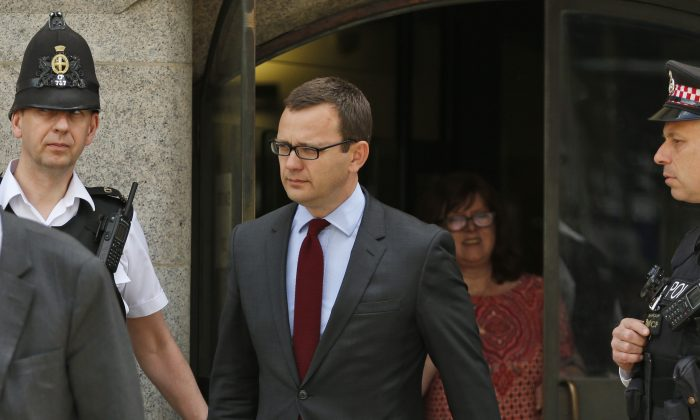 Andy Coulson, left, former News of the World editor and the former spin doctor of British Prime Minister David Cameron, leaves the Central Criminal Court in London, Wednesday, June 25, 2014. (AP Photo/Lefteris Pitarakis)