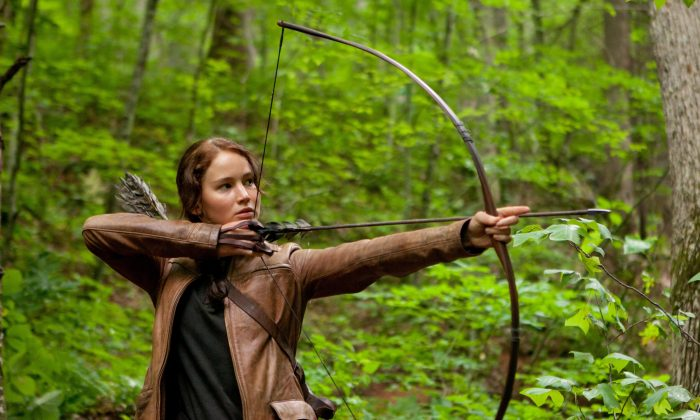 "FILE - In this image released by Lionsgate, Jennifer Lawrence portrays Katniss Everdeen in a scene from ""The Hunger Games."" A fictional gesture from a Hollywood movie is being used as a real symbol of resistance in Thailand. Protesters against a military coup are flashing the three-finger salute from ""The Hunger Games"" as a silent act of rebellion, and they're being threatened with arrest if they ignore warnings to stop. (AP Photo/Lionsgate, Murray Close, File)"