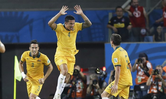 Australia's Tim Cahill (4) celebrates with Mark Milligan (5) and Jason Davidson (3) after Cahill scored his side's first goal during the first half of the group B World Cup soccer match between Chile and Australia in the Arena Pantanal in Cuiaba, Brazil, Friday, June 13, 2014. (AP Photo/Thanassis Stavrakis)