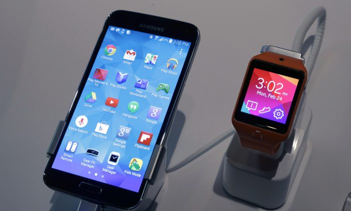A Samsung Galaxy S5 smartphone, left, and a Samsung Gear 2 are displayed at the Samsung Galaxy Studio, in New York. Samsung's latest gadgets, the Galaxy S5 smartphone, Gear Fit wristband and Gear 2 and Gear 2 Neo wristwatches, try to tap into people's passions for tracking fitness activities. (AP Photo/Richard Drew)