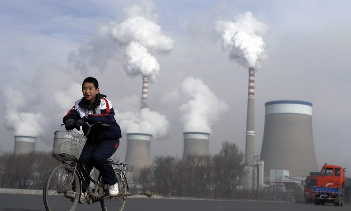 A Chinese boy cycles past a cooling towers of a coal-fired power plant in Dadong, Shanxi Province, China, on Dec. 3, 2009. (Andy Wong/AP)