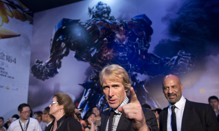 """In this Monday June 23, 2014 photo, director Michael Bay, center, gestures to fans as he attends the premiere of movie """"Transformers: Age of Extinction"""" at a theatre in Beijing, China. The fourth installment of the Michael Bay-directed franchise has gone all-out to woo China's audience with Chinese locations, talent and even a reality TV show. """"Transformers: Age of Extinction"""" illustrates the delicate balancing game of Hollywood studios trying to work out what the Chinese market wants while simultaneously catering to Americans. (AP Photo/Alexander F. Yuan)"""