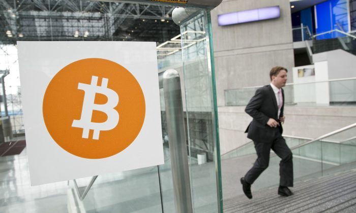 In this April 7, 2014 file photo, a man arrives for the Inside Bitcoins conference and trade show in New York. (AP Photo/Mark Lennihan, File)
