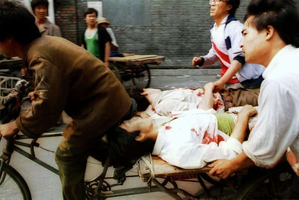 In this June 4, 1989, photo a rickshaw driver peddles wounded people, with the help of bystanders, to a nearby hospital in Beijing after they were injured during clashes with Chinese soldiers in Tiananmen Square. The crackdown ended a period of relative political openness, led to the downfall of Communist Party leader Zhao Ziyang and plunged Beijing into diplomatic isolation that lasted until the late 1990s. (AP Photo/Liu Heung Shing)