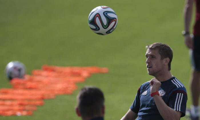 Dmitry Kombarov heads the ball during the Russian national soccer team's training session in Itu, Brazil, on Saturday, June 14, 2014. Russia will play in group H of the 2014 soccer World Cup. (AP Photo/Ivan Sekretarev)
