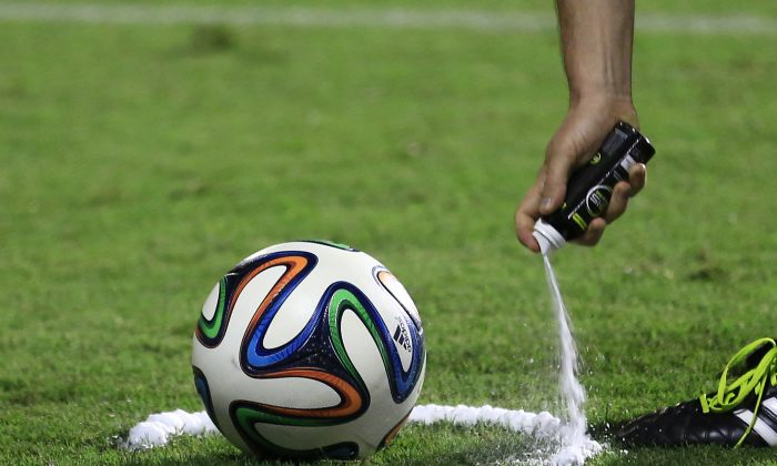 A referee uses vanishing spray during a referee's training session in Rio de Janeiro, Brazil, Friday, June 6, 2014. Referees will use vanishing spray during 2014 World Cup to stop defensive walls creeping forward at free-kicks. The international soccer tournament is set to begin in a few days, with Brazil and Croatia competing in the opening match on June 12. (AP Photo/Hassan Ammar)