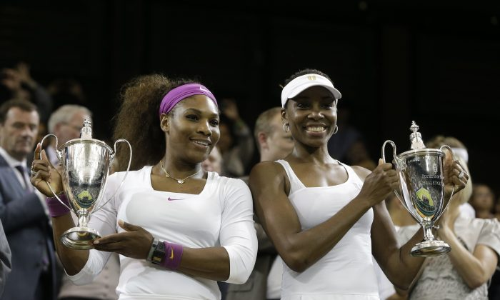 Serena Williams and Venus Williams of the United States, hold the trophy  after defeating Andrea Hlavackova and Lucie Hradecka of the Czech Republic in the women's doubles final match at the All England Lawn Tennis Championships at Wimbledon, England, Saturday, July 7, 2012. (AP Photo/Kirsty Wigglesworth)