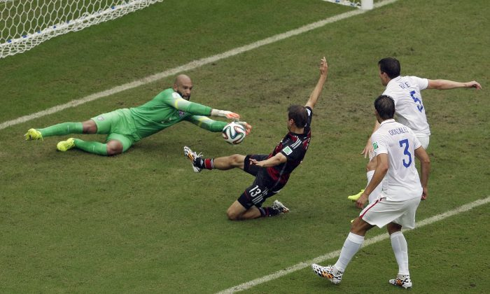 Germany's Thomas Mueller, center, takes a shot which is stopped by United States' goalkeeper Tim Howard as United States' Omar Gonzalez (3) and Matt Besler (5), move into the play during the group G World Cup soccer match between the USA and Germany at the Arena Pernambuco in Recife, Brazil, Thursday, June 26, 2014. (AP Photo/Hassan Ammar)