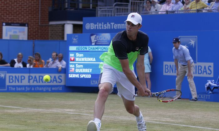 Sam Querrey of U.S. plays a return to Stan Wawrinka of Switzerland during their Queen's Club grass court championships 3rd round tennis match in London, Thursday, June 12, 2014. (AP Photo/Sang Tan)