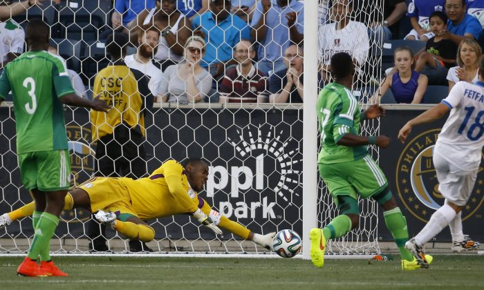 Nigeria goalkeeper Vincent Enyeama, center, dives to block a shot by Greece midfielder Ioannis Fetfatzidis, right, as defender Elderson Echiéjilé, left, and midfielder Ogenyi Onazi look on during the first half of an an international friendly soccer match, Tuesday, June 3, 2014, in Chester, Pa. (AP Photo/Matt Slocum)