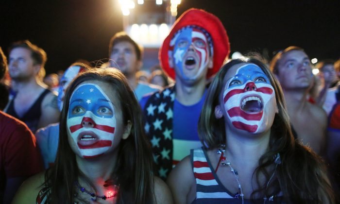 JUNE 23: Fans with their faces painted with the U.S. national colors, watch a live telecast of the World Cup match between United States and Portugal, inside the FIFA Fan Fest area on Copacabana beach, in Rio de Janeiro, on June 22, 2014. (AP Photo/Leo Correa)