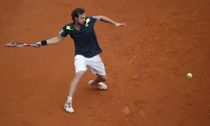 Latvia's Ernests Gulbis returns the ball to Switzerland's Roger Federer during their fourth round match of  the French Open tennis tournament at the Roland Garros stadium, in Paris, France, Sunday, June 1, 2014. (AP Photo/Michel Euler)