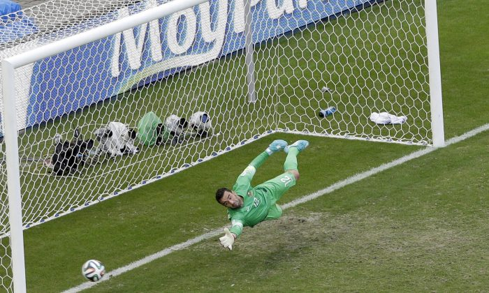 A penalty shot by Germany's Thomas Mueller goes into the net past Portugal's goalkeeper Eduardo during the group G World Cup soccer match between Germany and Portugal at the Arena Fonte Nova in Salvador, Brazil, Monday, June 16, 2014. At right Portugal's Pepe and Portugal's Joao Pereira.(AP Photo/Christophe Ena)