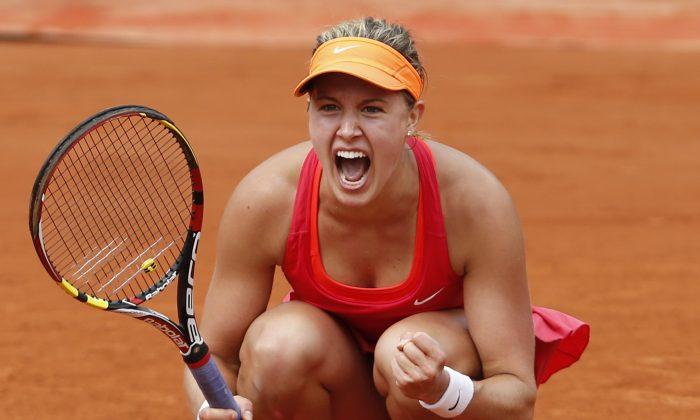 Canada's Eugenie Bouchard celebrates winning the quarterfinal match of the French Open tennis tournament against Spain's Carla Suarez Navarro at the Roland Garros stadium, in Paris, France, Tuesday, June 3, 2014. Bouchard won in three sets 7-6, 2-6, 7-5. (AP Photo/Darko Vojinovic)
