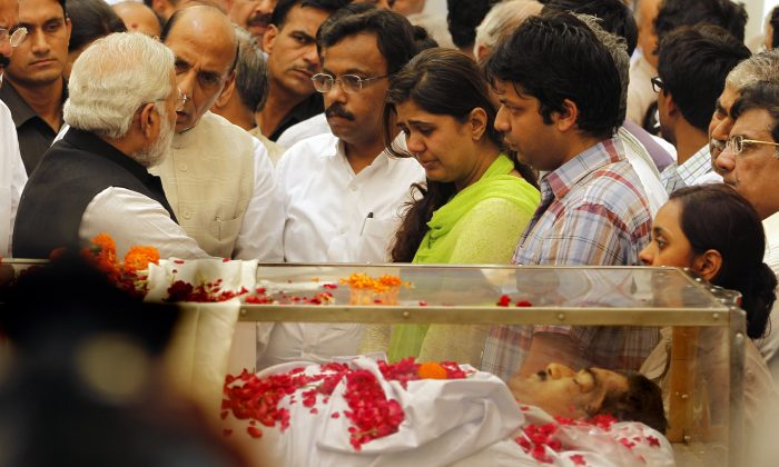 Indian Prime Minister Narendra Modi, left, speaks to the relatives of India's Rural Affairs Minister Gopinath Munde in New Delhi, India, Tuesday, June 3, 2014. Munde was killed in a car accident Tuesday in New Delhi. (AP Photo/Altaf Qadri)