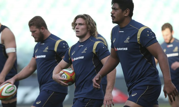 Australia captain Michael Hooper center, warms up during the captains run in Sydney, Australia, Friday, June 20, 2014.  Australia play France in the third test in Sydney, Saturday, June 21, 2014 with the Wallabies leading the series 2-0.(AP Photo/Rob Griffith)