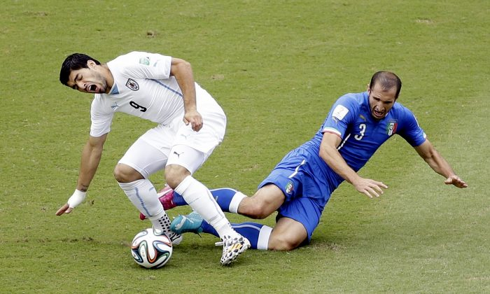 Uruguay's Luis Suarez (9) battles Italy's Giorgio Chiellini (3) for the ball during the group D World Cup soccer match between Italy and Uruguay at the Arena das Dunas in Natal, Brazil, Tuesday, June 24, 2014. (AP Photo/Hassan Ammar)
