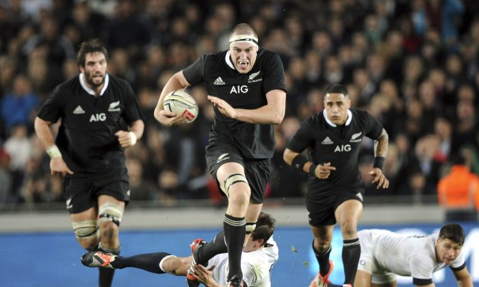 New Zealand's Brodie Retallick slips the tackle of England's Freddie Burns in the International Rugby Test at Eden Park, Auckland, New Zealand, Saturday, June 07, 2014. (AP Photo/SNPA, Ross Setford)