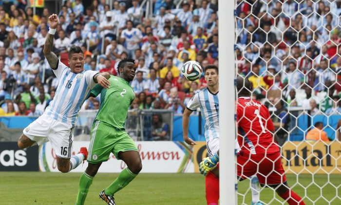 Argentina's Marcos Rojo watches as a header against Nigeria's Joseph Yobo moves toward Nigeria's goal during their group F World Cup soccer match at the Estadio Beira-Rio in Porto Alegre, Brazil, Wednesday, June 25, 2014. (AP Photo/Jon Super)