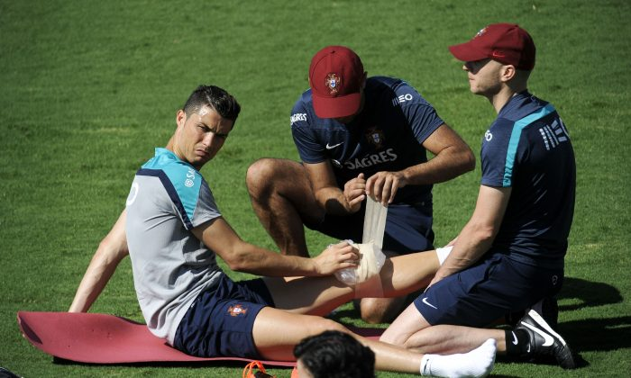 Cristiano Ronaldo has ice put on his left knee after a training session of Portugal in Campinas, Brazil, Wednesday, June 18, 2014. Portugal plays in group G of the Brazil 2014 soccer World Cup. (AP Photo/Paulo Duarte)