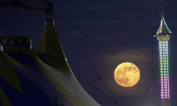 The moon rises between a tent, left, and a ride at State Fair Meadowlands, Sunday, June 23, 2013, in East Rutherford, N.J. The so-called supermoon appeared up to 14 percent larger than normal this weekend as our celestial neighbor swung closer to Earth, reaching its closest distance early Sunday morning. (AP Photo/Julio Cortez)