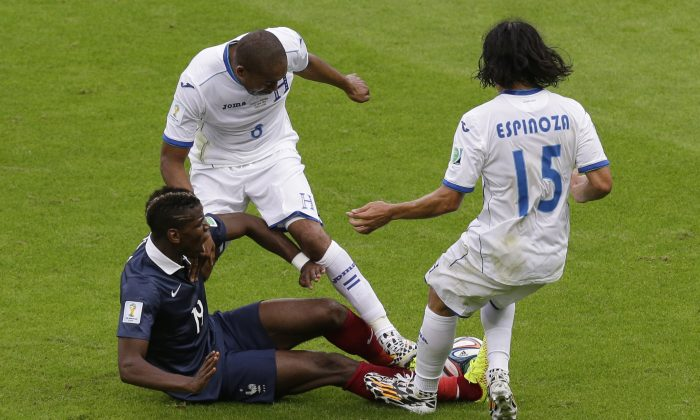 France's Paul Pogba, left, and Honduras' Wilson Palacios and Roger Espinoza, right, challenge for the ball during the group E World Cup soccer match between France and Honduras at the Estadio Beira-Rio in Porto Alegre, Brazil, Sunday, June 15, 2014.  (AP Photo/Andrew Medichini)