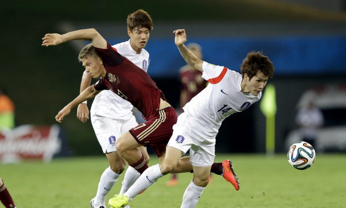 Russia's Oleg Shatov, left, and South Korea's Han Kook-young battle for the ball during the group H World Cup soccer match between Russia and South Korea at the Arena Pantanal in Cuiaba, Brazil, Tuesday, June 17, 2014. (AP Photo/Kirsty Wigglesworth)