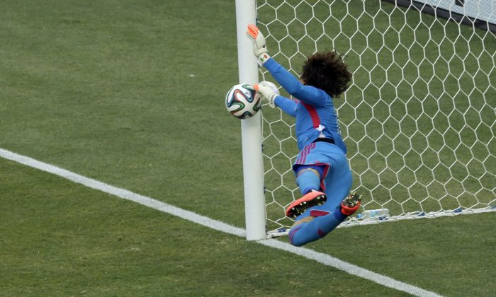 Mexico's goalkeeper Guillermo Ochoa makes a save during the group A World Cup soccer match between Brazil and Mexico at the Arena Castelao in Fortaleza, Brazil, Tuesday, June 17, 2014.  (AP Photo/Themba Hadebe)