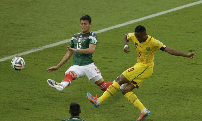 Cameroon's Samuel Eto'o shoots as Mexico's Hector Moreno defends during the group A World Cup soccer match between Mexico and Cameroon in the Arena das Dunas in Natal, Brazil, Friday, June 13, 2014.  (AP Photo/Hassan Ammar)