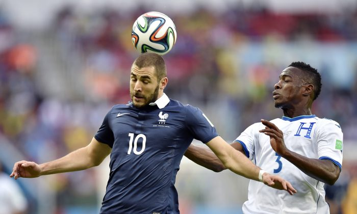 France's Karim Benzema heads the ball away from Honduras' Maynor Figueroa during the group E World Cup soccer match between France and Honduras at the Estadio Beira-Rio in Porto Alegre, Brazil, Sunday, June 15, 2014.  (AP Photo/Martin Meissner)