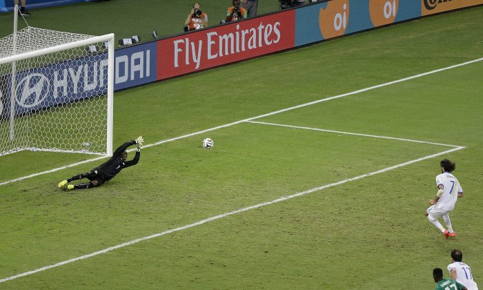 Greece's Giorgos Samaras (7) fires off a shot over Ivory Coast's goalkeeper Boubacar Barry to score on a penalty kick in the final minutes during the group C World Cup soccer match between Greece and Ivory Coast at the Arena Castelao in Fortaleza, Brazil, Tuesday, June 24, 2014. Greece won 2-1. (AP Photo/Sergei Grits)
