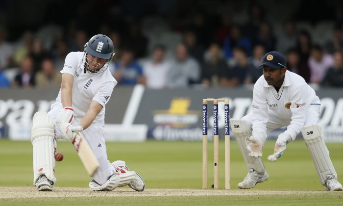 England's Gary Ballance hits a six to complete his maiden test 100 runs not out off the bowling of Sri Lanka's Rangana Herath on the fourth day of the first Test cricket match between England and Sri Lanka at Lord's cricket ground in London, Sunday, June, 15, 2014. (AP Photo/Alastair Grant)