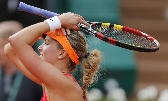 Canada's Eugenie Bouchard smiles after defeating Spain's Carla Suarez Navarro during their quarterfinal match of  the French Open tennis tournament at the Roland Garros stadium, in Paris, France, Tuesday, June 3, 2014. Bouchard won 7-6, 2-6, 7-5.  (AP Photo/David Vincent)
