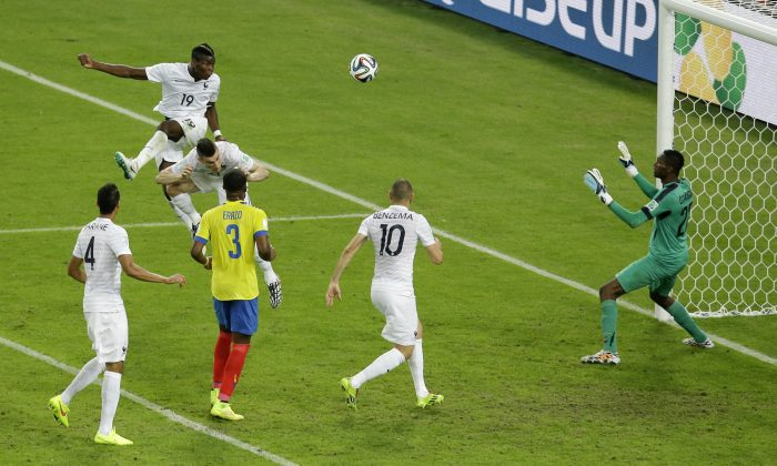 France's Paul Pogba (19) heads the ball towards the goal which was stopped by Ecuador's goalkeeper Alexander Dominguez during the group E World Cup soccer match between Ecuador and France at the Maracana Stadium in Rio de Janeiro, Brazil, Wednesday, June 25, 2014. (AP Photo/Andrew Medichini)