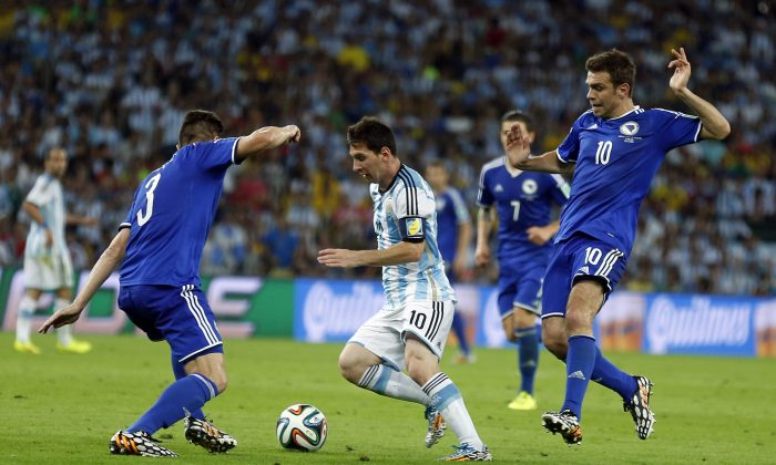 Argentina's Lionel Messi, centre, runs at the Bosnian defense during the group F World Cup soccer match between Argentina and Bosnia at the Maracana Stadium in Rio de Janeiro, Brazil, Sunday, June 15, 2014.  (AP Photo/Victor R. Caivano)