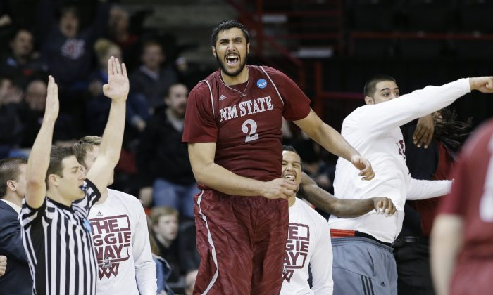 New Mexico State's Sim Bhullar yells from the bench against San Diego State in the second half during the second round of the NCAA men's college basketball tournament in Spokane, Wash., Thursday, March 20, 2014. (AP Photo/Elaine Thompson)